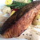Crispy skinned salmon , roasted potatoes, sautéed vegetables & bacon horseradish sauce.
