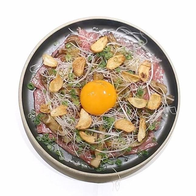 Ron in's Kagoshima Beef topped with maitake mushrooms, negi, and a sukiyaki egg yolk.