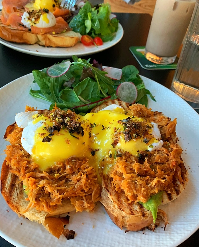Open-faced sandwich with pulled pork and poached eggs