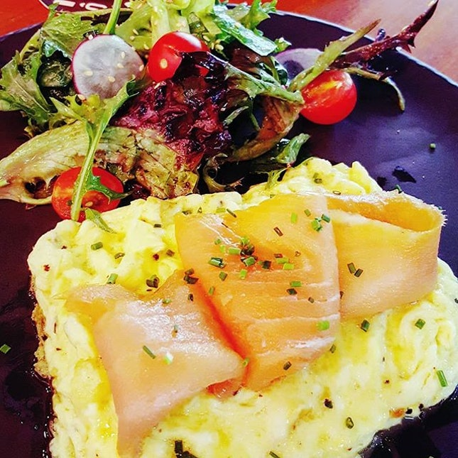 🍳: Luscious ribbons of smoked salmon draped on a bed of scrambled eggs.
