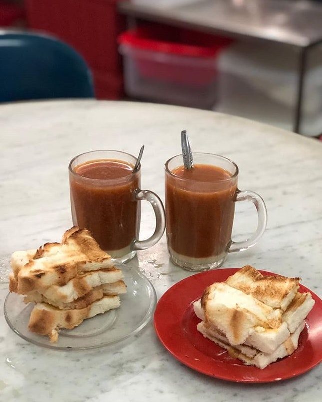 The quintessential Singaporean breakfast of Kaya and butter on toast and a cup of coffee or milk tea.