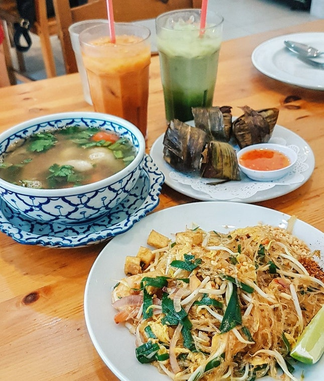 Nothing beats an affordable Thai meal! On the table is the clear seafood tom yum soup, pandan leaves chicken, pad thai, and Thai iced milk tea 😋