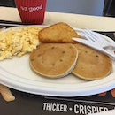 Blueberry pancakes with scrambled eggs and hashbrown.