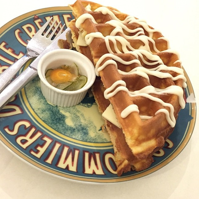 Fluffy waffles with ham and cheese drizzled with cheese.