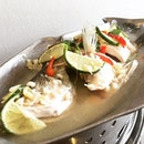 Pla Neung Manao  Steamed Fish with Spicy Lime Sauce  A steamed sea bass is submerged into a refreshing and zesty blend of lime and chilli soup with a host of Thai garnishing such as corianders and garlic cloves.