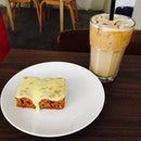 A nice small carrot cake with iced latte.