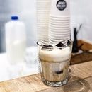 Stronger and stronger - an empty cup filled to the brim with espresso ice cubes, with milk added upon service.