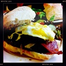 Having the Kitchen Sink Burger: Juicy beef patty, bacon, caramalised onion, portobello & egg