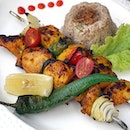 Shish Taouk ($20) Traditional chicken shish kebab marinated overnight with Lebanese herbs & spices served alongside oriental Arabic rice & vegetables.