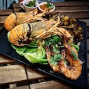 (MEDIA INVITE) A seafood platter consisting of 2 lobsters, 3 big tiger prawns and grilled potatoes garnished with greens.