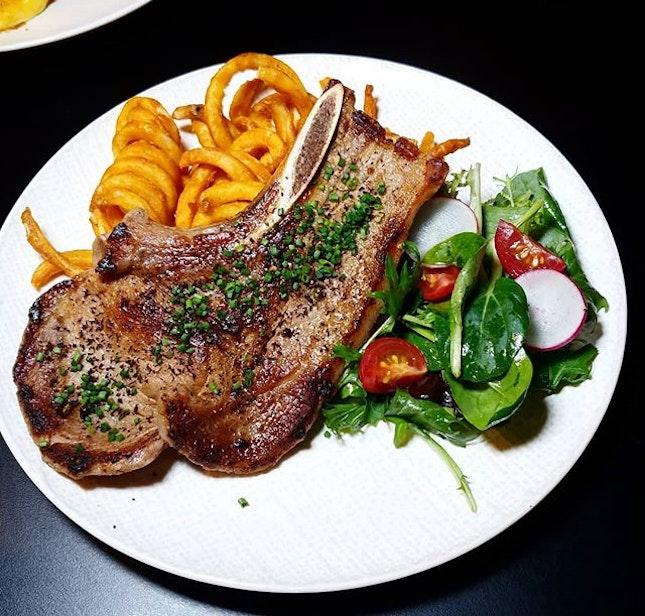 US Kurobuta Bone-in Pork Chop $29, with curly fries and mesclun salad.