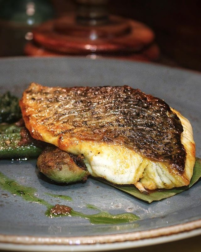 Pan-Seared Sea-Bass, Sourced locally, subject yield a moist and tender doneness, resting on a bed of Aubergine Okra stir-fried in Sambal Chilli.