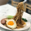 Dry noodles with fried egg [$4.80] Served with your choice of ham or luncheon meat, these dry noodles are tossed in braised dark soy sauce and topped off with a sunny side up and bok choy.