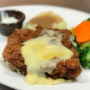 Crispy chicken with Swiss raclette cheese [$15.90] With your choice of 2 sides, this deep fried chicken cutlet is topped with Swiss raclette cheese and served with a side of mayonnaise (?).