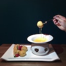 Salted egg yolk and white chocolate fondue • Paired with mini custard profiteroles .