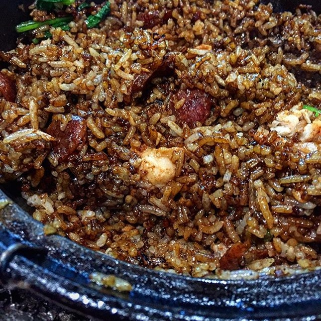 """Claypot rice is essentially rice cooked in Claypot with chicken (sometimes marinated), Chinese sausage and salted fish (colloquially known as """"Ham Yu""""); oh and throw in a couple of leafy green vegetables."""