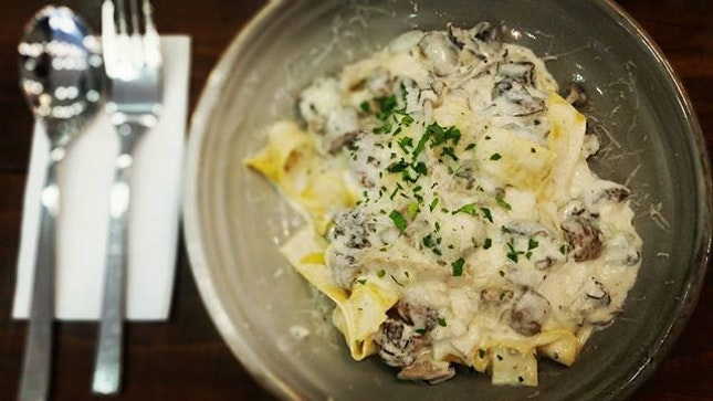 Pappardelle al Funghi - al dente flat pasta swirling in thick creamy white sauce with many different types of mushrooms and topped with cheese sprinkles...