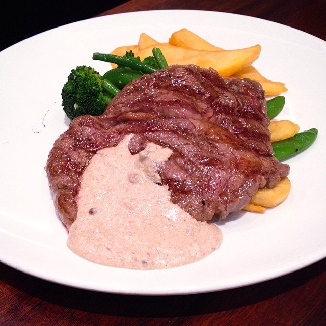 """Char-grilled ribeye with """"pink peppercorn"""", served with fries and spring vegetables."""