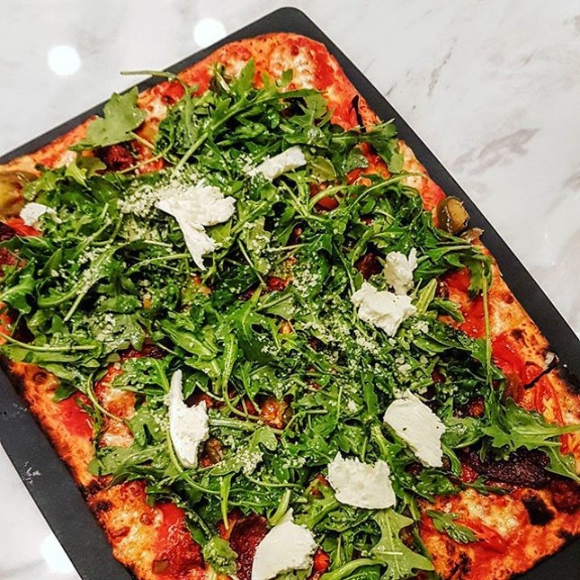 Calabrese Pizza with a very thin and crispy crust, fresh tomato base, spicy sliced sausages (my favorite part) and jalapenos topped with pesto, arugula and chunks of fresh mozzarella...